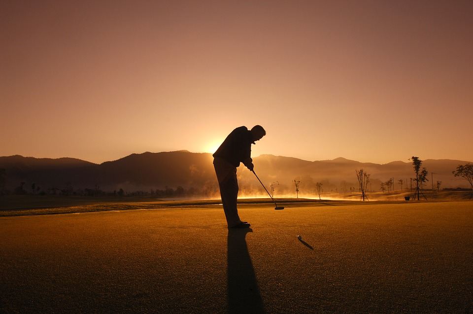 person doing golf during midnight sun