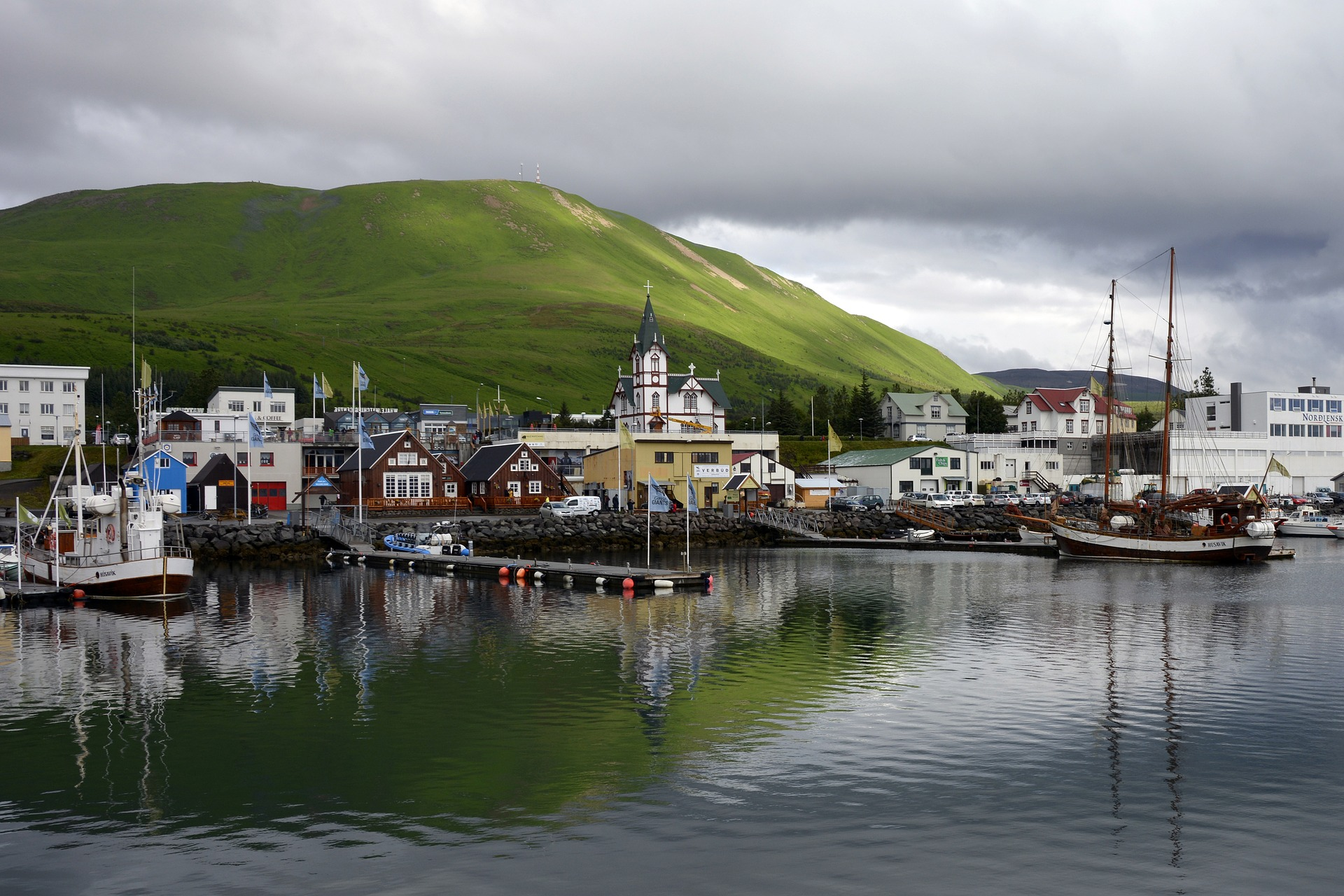 Husavik harbor and town with boats, and mountains on the background