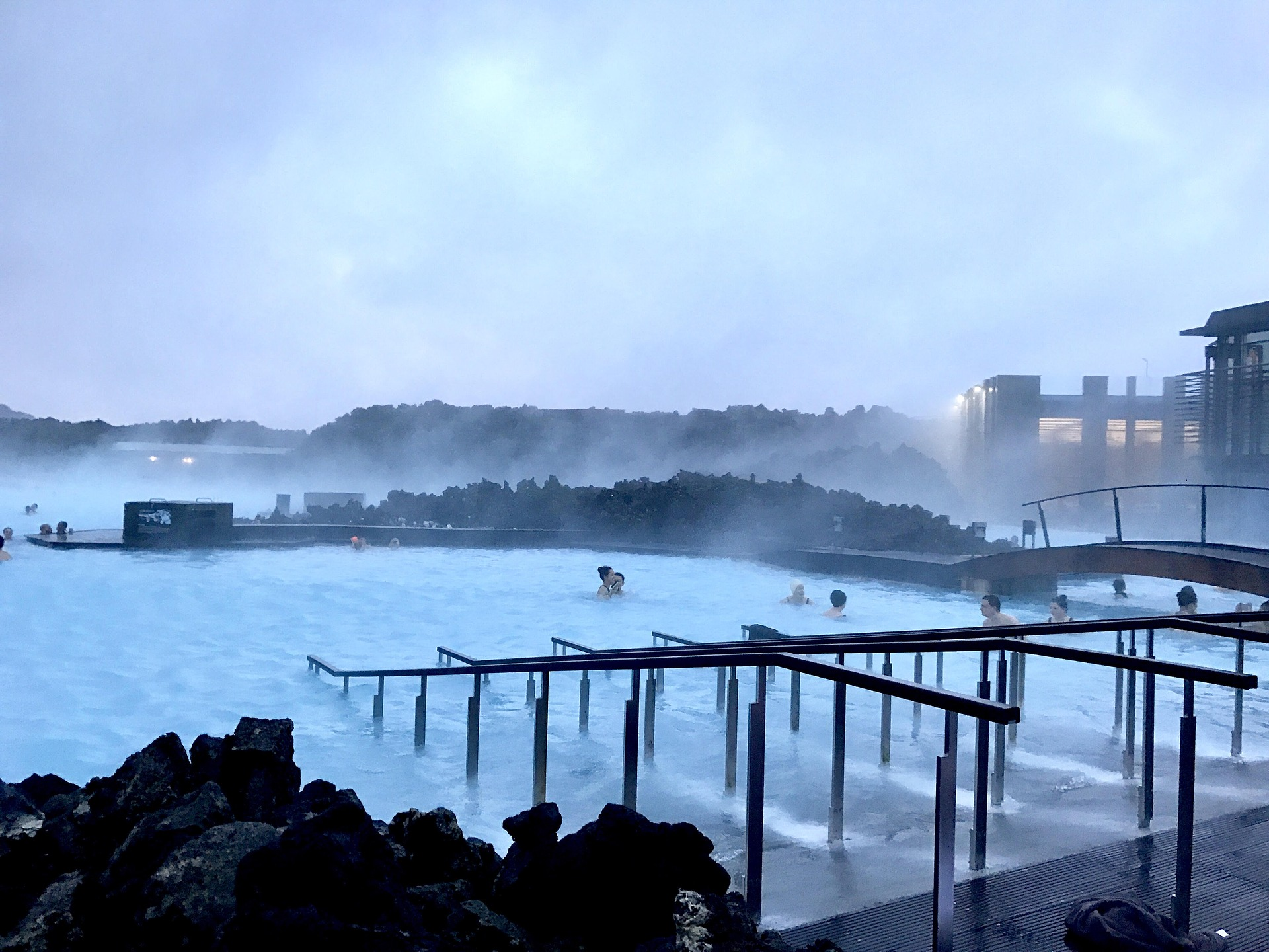 blue lagoon in iceland, with stairs to go to the lagoon, people are bathing in hot waters