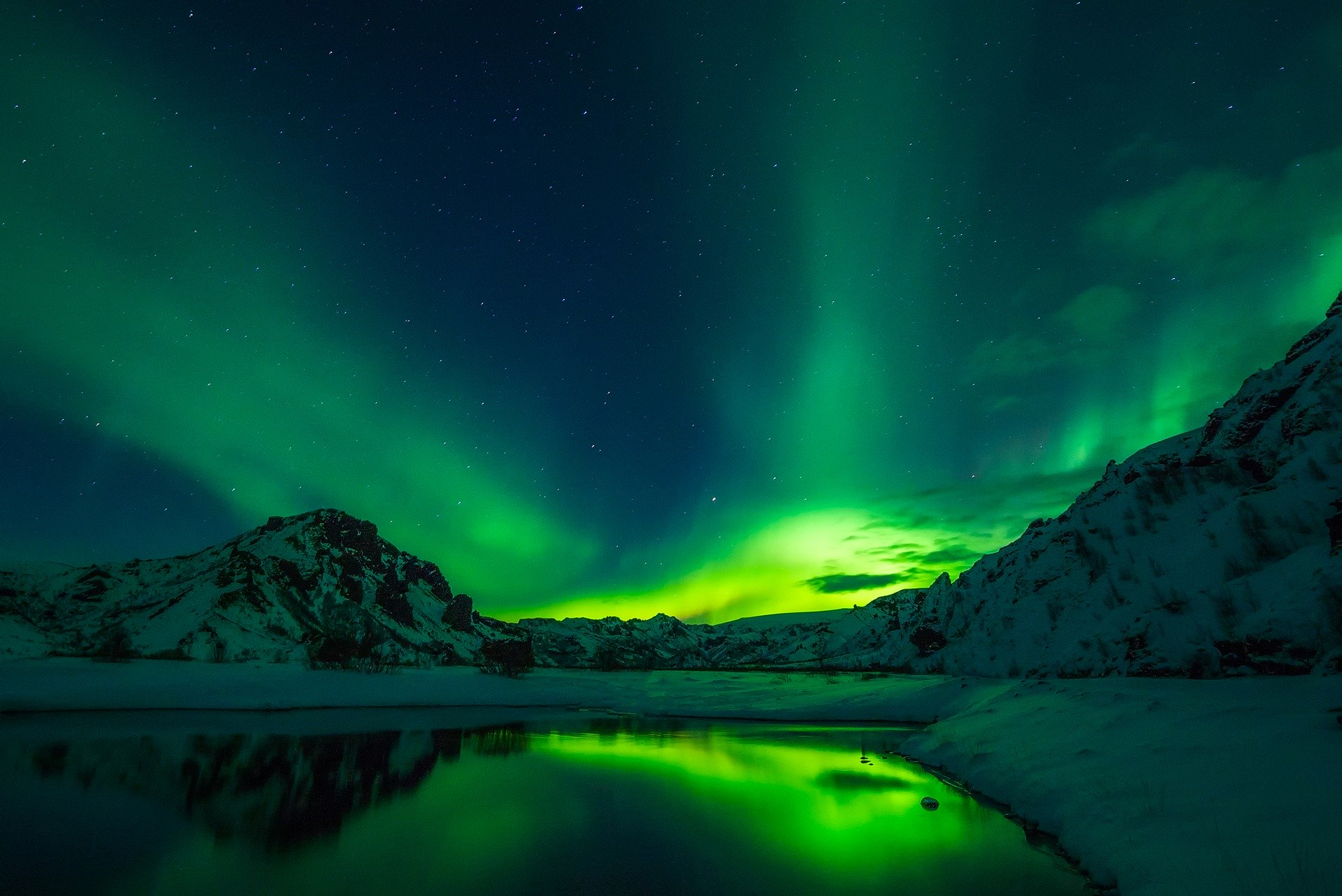 Green northern lights in iceland at night, lake one the foreground, mountains on the background
