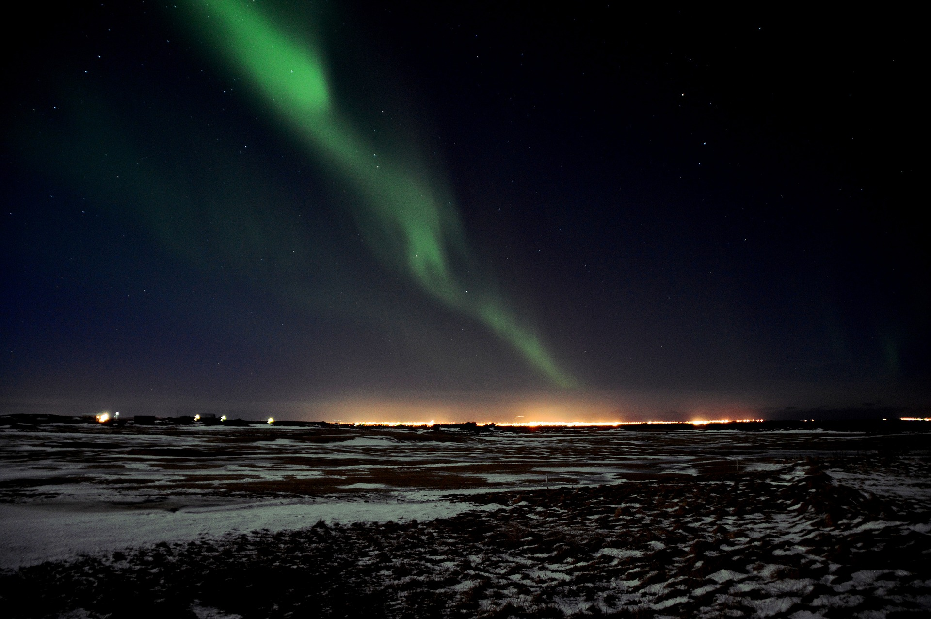 Northern light in Iceland with light pollution on the back ground