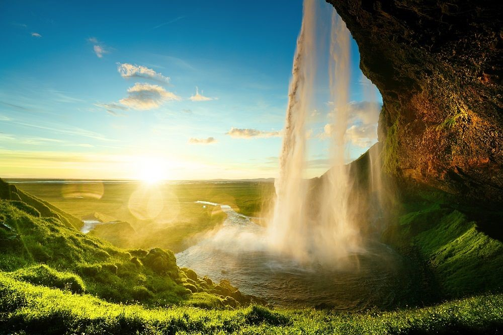 seljalandsfoss waterfall in Iceland with the sun, viewed from behind the falling water