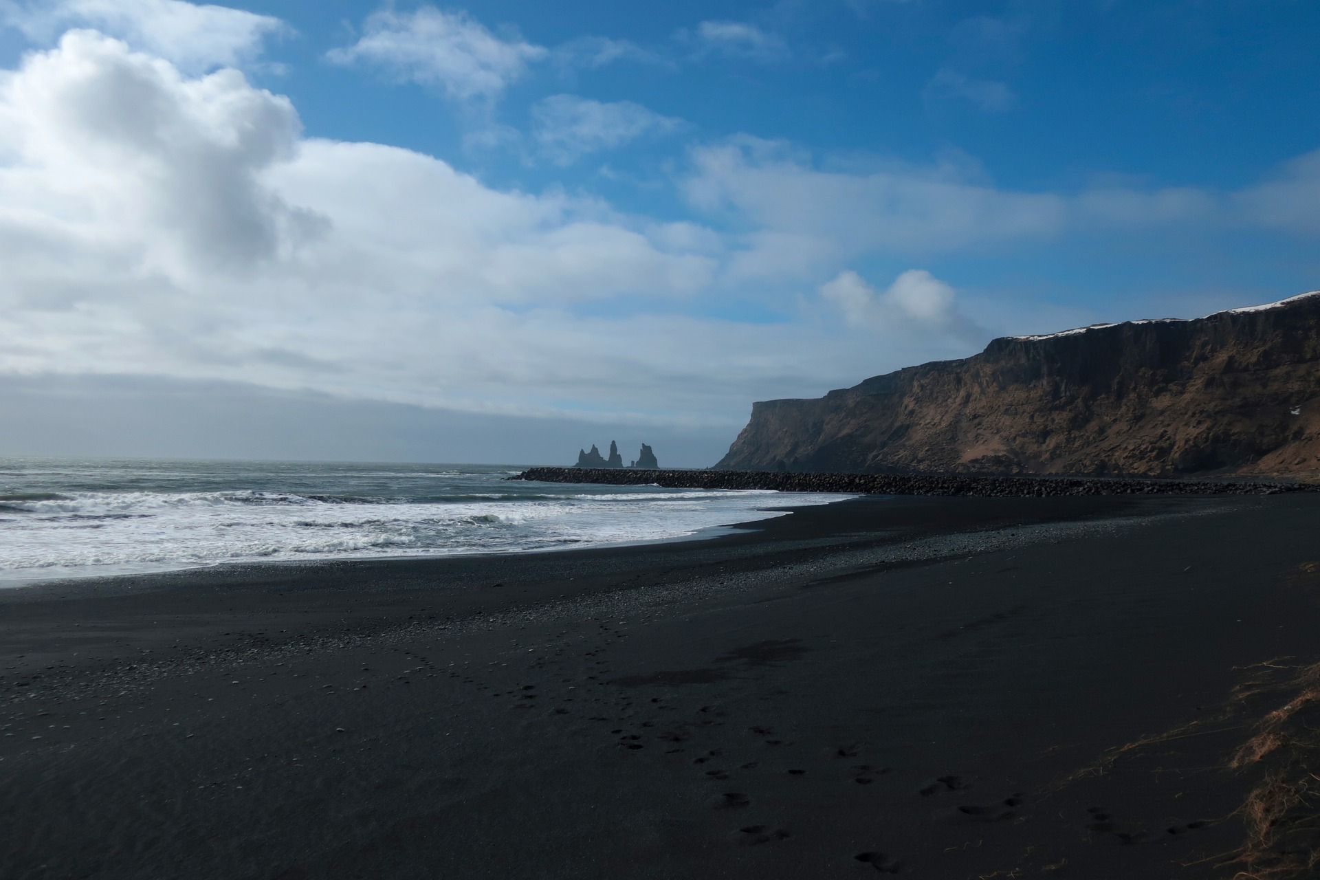 black sand beach in vik in iceland, cliffs, sea, waves, blue sky